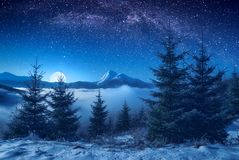 Beautiful mountain peak on a horizon at night. Winter valley covered with fresh snow in a light of rising moon. Beautiful mountain peak on a horizon. Fantastic Royalty Free Stock Image