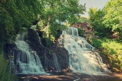 High mountain waterfall. Beautiful mountain rainforest waterfall with fast flowing water and rocks, long exposure. Natural seasonal travel outdoor background in Stock Images