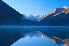 Beautiful mountain range are reflected in foggy lake Royalty Free Stock Photography