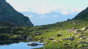 Beautiful mountain scenery, green rocky valley with clear lake. Stock footage stock video footage