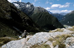 Beautiful Mountain Scenery on Hike. A hiker walking along a valley trail in the middle of the spectacular mountain scenery of Routeburn Trail near Routeburn Stock Image