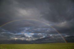 Beautiful mountain valley rain storm over hay field with a rainb Royalty Free Stock Photos