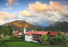 Beautiful mountain village in evening ambience. Splendid sunset and alpenglow. Moody clouds are gathering above the valley in teh background. Bad Hindelang Stock Images