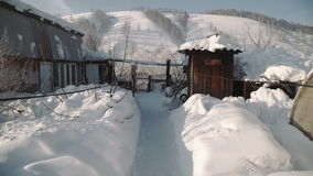 Beautiful mountain village in winter day, traditional house and car road covered by heavy snow stock video