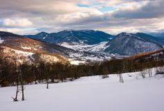 Beautiful mountainous countryside in afternoon. Gorgeous winter landscape with cloudy sky and snowy slopes Royalty Free Stock Photography