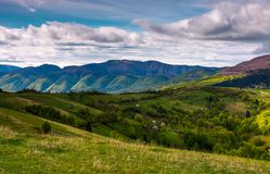 Beautiful mountainous countryside in springtime. Village outskirts with rural fields on rolling hills Stock Photo