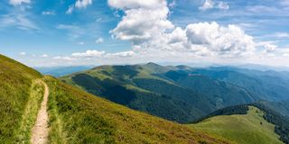 Beautiful mountainous landscape on fine summer day. Footpath running through grassy hillside under blue sky fluffy clouds. gorgeous panorama of mountain ridge Royalty Free Stock Images