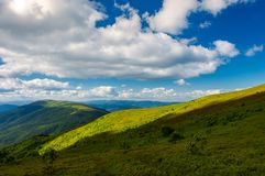 Beautiful mountainous landscape. Under the summer sky. fluffy clouds over the mountain ridge. light on the nearest hill. pleasant atmosphere and good day for a Royalty Free Stock Photos