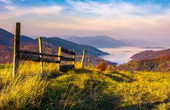 Beautiful mountainous landscape with wooden fence. Lovely autumnal scenery at sunrise with gorgeous sky over the valley full of fog royalty free stock photos