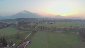 Beautiful mountains hiding sun on horizon, green farming fields, amazing sunrise. Stock footage stock video