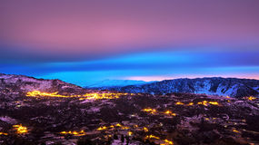 Beautiful mountains landscape. Amazing pink and blue sky over mountainous glowing city, beauty of nighttime, winter holidays concept royalty free stock photography