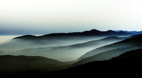 Beautiful mountains landscape from the top of the hill with fog Stock Images