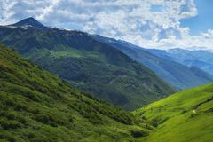 Beautiful mountains ranges. Mountain landscape on summer sunny day with white clouds in blue sky. Scenery nature of wild Svaneti stock image