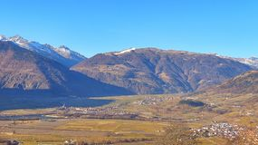 Beautiful Mountains and valley in Vinschgau Italia autumn landscape. Mountain village lying in a valley among the plantations of Apple trees: Glurns, Mals Stock Photo