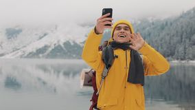 Beautiful mountains in winter time. Man with beard, wearing yellow winter clothes take selfie against the background of. Beautiful mountains and mountain lake stock video footage