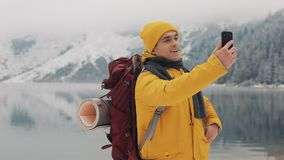 Beautiful mountains in winter time. Man with beard, wearing yellow winter clothes take selfie against the background of. Beautiful mountains and mountain lake stock footage