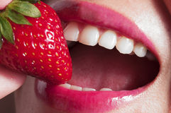Beautiful  mouth eating  strawberry Royalty Free Stock Photo