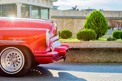 Beautiful moving blurry vintage old timer car from the sixties in a city center. Red vintage old timer car from the sixties in a city center Stock Photo