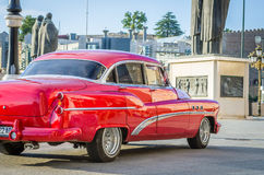 Beautiful moving vintage old timer car from the sixties in a city center. Red vintage old timer car from the sixties in a city center Stock Image