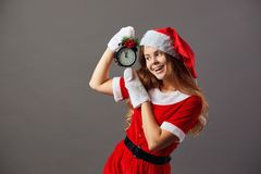 Beautiful mrs.Santa Claus dressed in the red robe, Santa`s hat and white gloves is holding a clock that shows five to. Twelve. Christmas Eve royalty free stock images