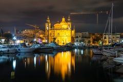 The beautiful Msida Parish Church at deep night with harbor at the foreground. Malta. Royalty Free Stock Photo