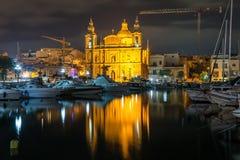 The beautiful Msida Parish Church at deep night with harbor at the foreground. Malta. Stock Images