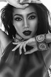 Beautiful mulatto brunette in ethnic accessories, and bracelet. Black and white fashion portrait of the beautiful mulatto whith dark skin, hair and red lips in Stock Photos