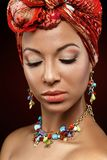 Beautiful mulatto young woman with turban on head. Beautiful mulatto young woman with orange turban on head. beauty shot on dark background. copy space Stock Photo