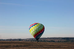 Beautiful multi-colored balloon lands in a field at the morning, Royalty Free Stock Photos