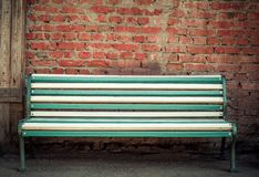 Beautiful multi-colored bench at a brick wall Royalty Free Stock Images