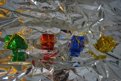 Beautiful multi-colored four packaged gifts for the holidays and the new year on a silver, metallic background, crumpled paper. A beautiful colorful background royalty free stock photo
