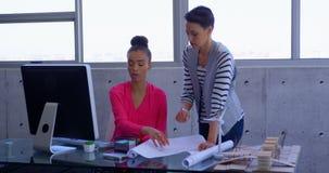 Beautiful multi-ethnic businesswomen working on desktop computer in modern office 4k. Front view of beautiful multi-ethnic businesswomen working on desktop in stock video footage
