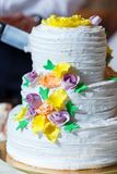 Beautiful multi level wedding cake. Groom in suit and bride in white dress cut beautiful multi level wedding cake, decorated with cream yellow flowers, greenery Royalty Free Stock Images