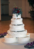 Beautiful Multi-tiered Wedding Cake. With white icing and red roses for decoration Stock Photos