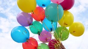 Beautiful multicolored balloons in the blue sky holds the hand. The concept of a wonderful holiday. color decorations at. Beautiful multicolored balloons in blue stock video
