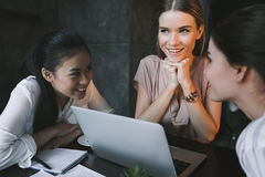 Beautiful multicultural businesswomen dreaming while sitting with laptop at cafe. Happy beautiful multicultural businesswomen dreaming while sitting with laptop Royalty Free Stock Image