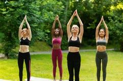Beautiful multinational girls doing sun salutations yoga flow at park