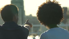 Beautiful multiracial couple looking at city from the roof at sunny day, date. Stock footage stock footage