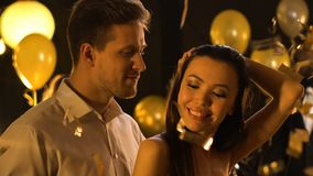 Beautiful multiracial couple seductively dancing under falling confetti, party. Stock footage stock footage