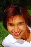 Beautiful multiracial woman. Outdoor portrait of an attractive young multiracial woman with happy smiling facial expression showing her beautiful white teeth and Stock Image