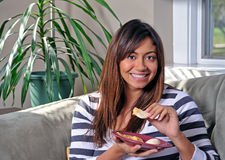 Beautiful multiracial woman eating hummus on couch Stock Image
