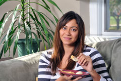Beautiful multiracial woman eating hummus on couch Royalty Free Stock Photography