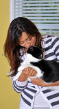 Beautiful multiracial woman kissing cat stock photo
