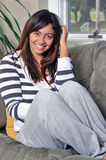 Beautiful multiracial woman sitting on couch Stock Photo