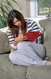 Beautiful multiracial woman writing in journal. Beautiful multiracial young woman sits on a couch, smiling, in a casual sweater and sweats writing in a red book royalty free stock image