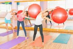 Beautiful multiracial women and man doing exercise with gimnastic ball. Stock Image
