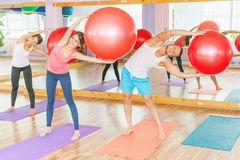Beautiful multiracial women and man doing exercise with gimnastic ball. Royalty Free Stock Photography