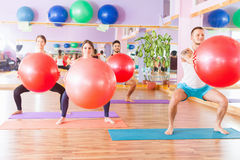 Beautiful multiracial women and man doing exercise with gimnastic ball. Stock Photo