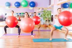 Beautiful multiracial women and man doing exercise with gimnastic ball. Stock Photo