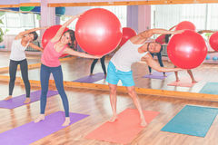 Beautiful multiracial women and man doing exercise with gimnastic ball. Stock Photography